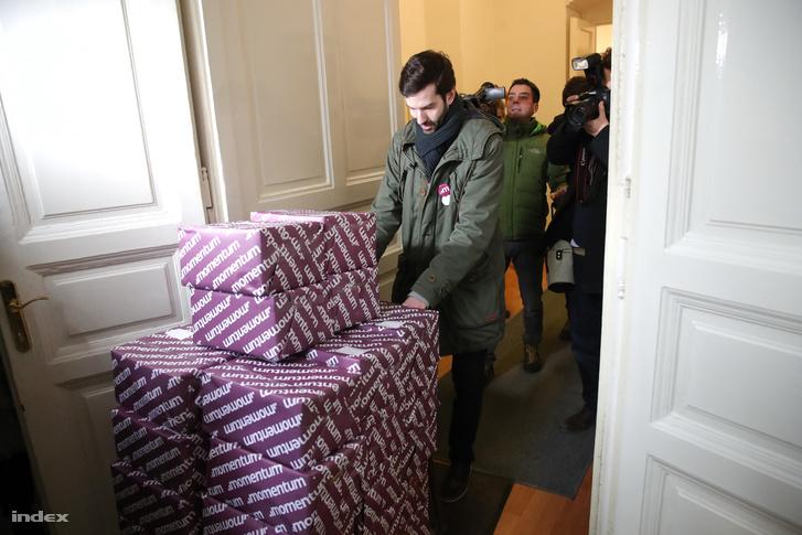 Fekete-Győr András betolja az aláírásokat tartalmazó dobozokat a Választási Iroda épületébe.