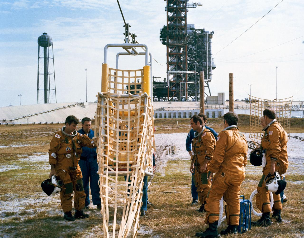1981. március. A NASA űrhajósai (John W. Young, Robert L. Crippen, Joe H. Engle, és Richard H. Truly) a startállás csúszódrótos mentőrendszerével ismerkednek. Baj esetén az űrhajósok a képen látható kosarakba szállva menekültek volna a startállásról.