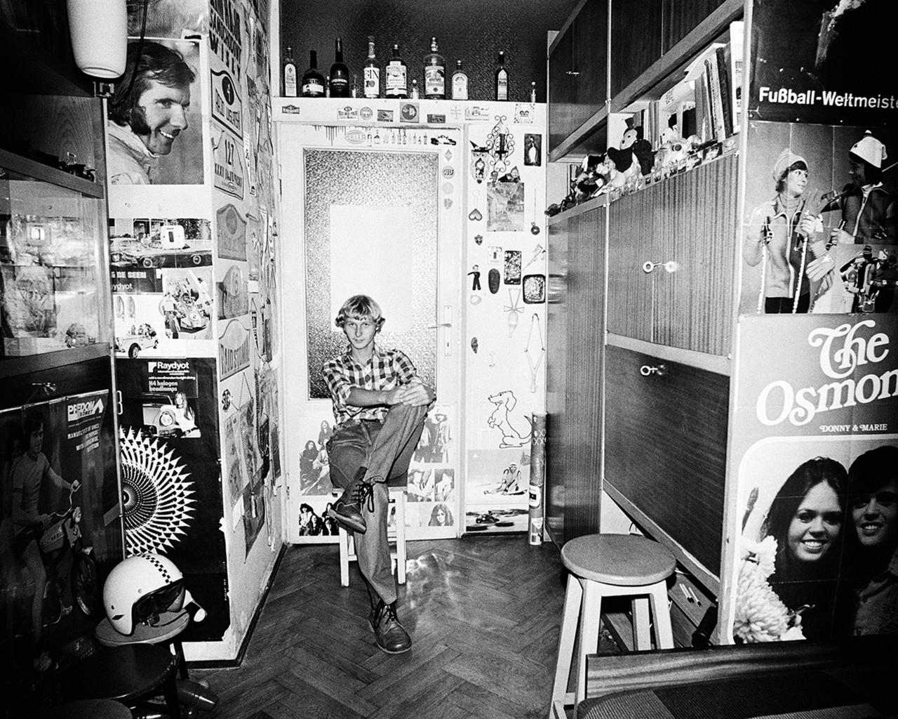 Jackie Stewart, The Osmonds, márkás nyugati italok és saját bukó a szekrénysor előtt. Rydet időnként belenyúlt a környezetbe: a felvétel előtt némileg átrendezte a szobában lévő tárgyakat, kisebb kompozíciót hozott létre az asztalon lévő dolgokból, egy-egy fotót a falon áthelyezett.