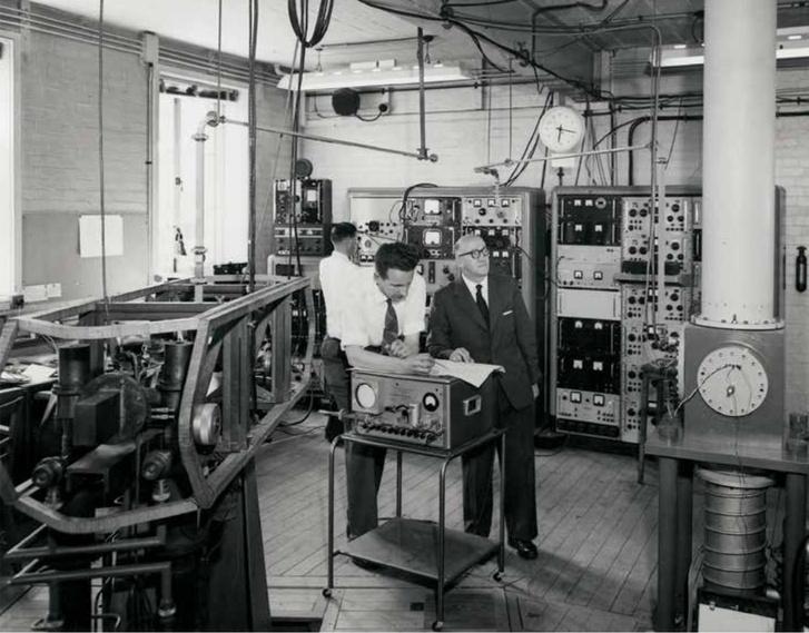 Louis Essen (jobbra, öltönyben) és az atomóra (balra, állványon) az NPL laborjában, 1962-ben.
