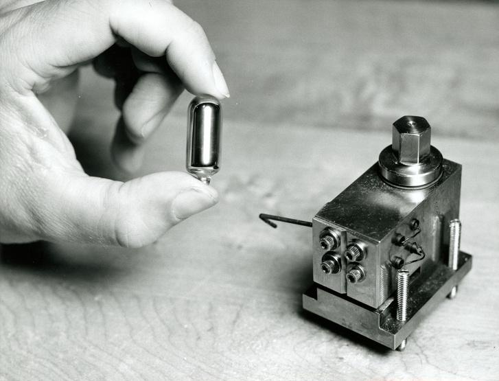 """A cézium-133, a cézium egyetlen stabil izotópja a lelke az atomórának. A magas hőmérsékleten elpárologtatott céziumatomok egész pontosan 9 192 631 770-szor rezegnek másodpercenként. A képen a folyékony céziumot tartalmazó kapszula látható, az alkáli fémet a mellette lévő """"sütőben"""" hevítik gőzzé."""