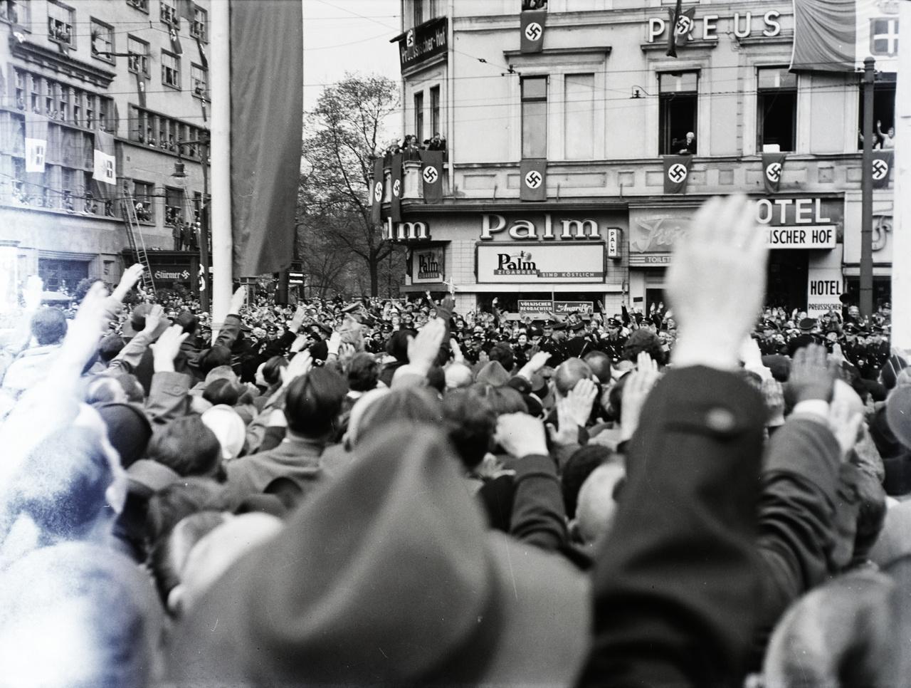 """A Führer megérkezett, nyitott autóban állva köszönti a berlinieket - profilját a kép közepétől balra könnyen ki lehet venni. Goebbels propagandaminiszter pontos utasításokban  instruálta Berlin népét, miként illik megünnepelni ezt a napot. """"Millió kéz intsen neki, millió száj kiáltsa feléje az egész lakosság háláját, senkinek sem szabad hiányozni az utcákról, ha a Führer jön. Zárjátok be üzemeiteket és egyetlen épület, üzlet, lakás ne legyen girland és zászlódísz  nélkül. Éljen Hitler, éljen népünk és az egész  birodalom!"""""""