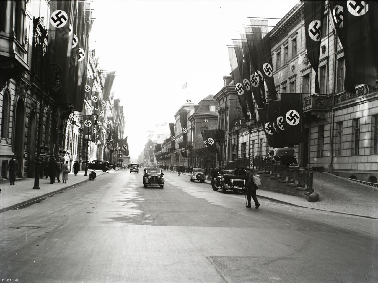 """A Wilhelmstrasse horogkeresztes zászlódíszben. A Berlint kiválóan ismerő, a városban éveket élt Keresztury Dezső írta 1939-ben a Nyugatban: """"Aki csak egy kicsit is figyelemmel kísérte az utolsó évtizedek fejlődését, világosan láthatta, hogy a Harmadik Birodalom a vidék forradalmi álmaiból született meg; a párt csak akkor foglalta el a fővárost, mikor a vidéken már meghódította a szíveket. A birodalom mai vezetői a régi szakadékot akarják mindenekelőtt áthidalni. Mióta meghódították Berlint, céltudatosan törekszenek arra, hogy a bensőséges, kisvárosias porosz főváros s a légüres térbe került világváros utódjaként megteremtsék a birodalom igazi fővárosát."""""""