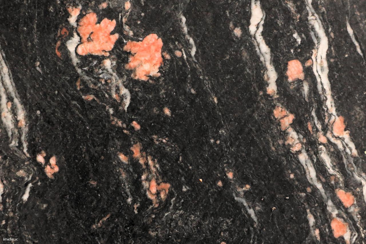 A Lukács fürdő pénztáránál és a várócsarnokban a padlóburkolat fekete márványlapjaiban jól láthatók a felaprózódott rózsaszín földpátszemcsék, a fehér kvarckristályok és a sötét rétegszilikátok.