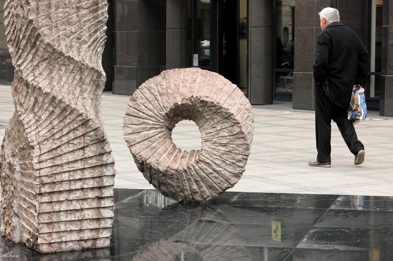 """A Bankcenter épülete előtt álló szoborcsoport, a két, kőből faragott, csavart oszlop és a """"Möbius-szalag"""" üledékes kőzetből, gerecsei, jura ammoniteszes mészkőből készült."""
