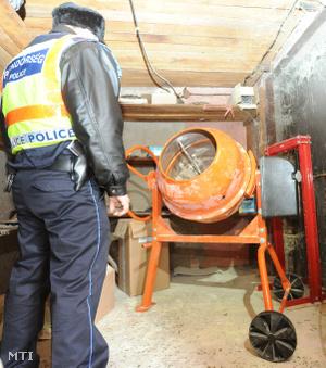 A lefoglalt színes porok és tabletták előállításához használt betonkeverőt nézi egy rendőr egy épületben a Pest megyei Pusztavacson 2013. február 7-én ahol új pszichoaktív anyagok előállításával foglalkozó labort számoltak fel.