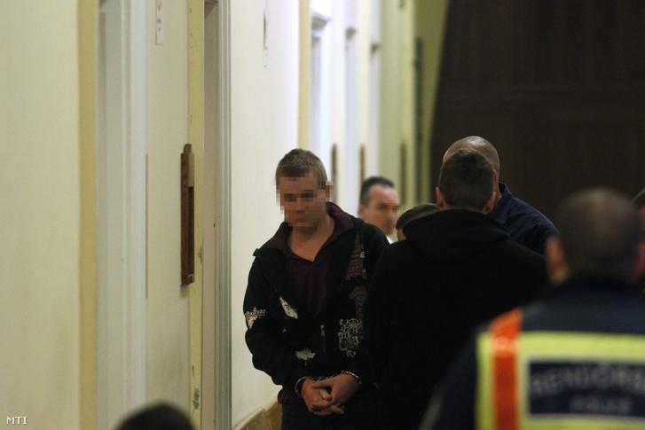 A Teréz körúti robbantás feltételezett elkövetőjét vezetik elő az előzetes letartóztatásról döntő tárgyalásra a Budai Központi Kerületi Bíróság folyosóján 2016. október 21-én.