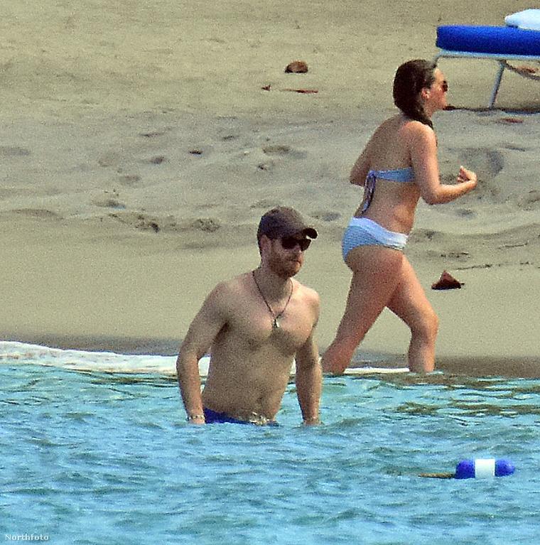 Harry herceg csupasz felsőtesttel, a háttérben barátnője, Meghan Markle.