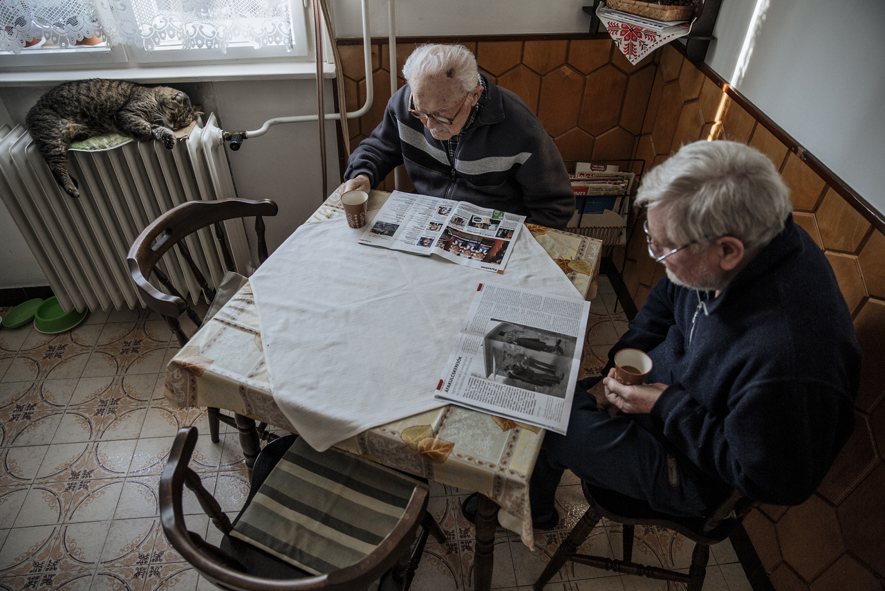 """""""Családi hagyomány, hogy a nap közös kávézással indul a kis ház konyhájában. Amíg nagypapa és apu elolvassa a híreket a radiátoron szundikáló Misi macska társaságában, a család nőtagjai gyakran még alszanak"""" - mondja Ajpek Orsi.""""Nagyszüleim még falun születtek, de fiatalon, nagyapám katonai szolgálata és a munka miatt Biharkeresztesről Marcaliba, majd 1956-ban Budapestre költöztek. Édesanyám már egy fővárosi bérházban nőtt fel velük. A dédszüleim nehezen viselték a távolságot, így némi rábeszélésre végül utánuk jöttek, és az akkor még falusias hangulatú Rákoshegyen találtak egy megfelelő házat, amit a család összes spórolt pénzét összerakva vásároltak meg 1962-ben"""" – mesél a fotográfus a házról, amiben a sorozatot készítette. Pár éve kezdte el fotózni a családtagjait, minden karácsonykor készített egy portrét a népes famíliáról, viszont ezeken az alkalmakon kívül nem fotózta őket. Most a Pannonhalmi Főapátság kiállítása miatt kezdte saját családját a mindennapokban megörökíteni. Azt mondja, a saját család fotózása egyfelől könnyebb, a meglévő bizalom miatt, másfelől nehezebb is, mert a legszemélyesebb történeteit és élettereit mutatja meg."""