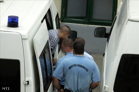 Fegyőrök elővezetik az egyik gyanúsítottat a Veszprémi Városi Bíróság épületében