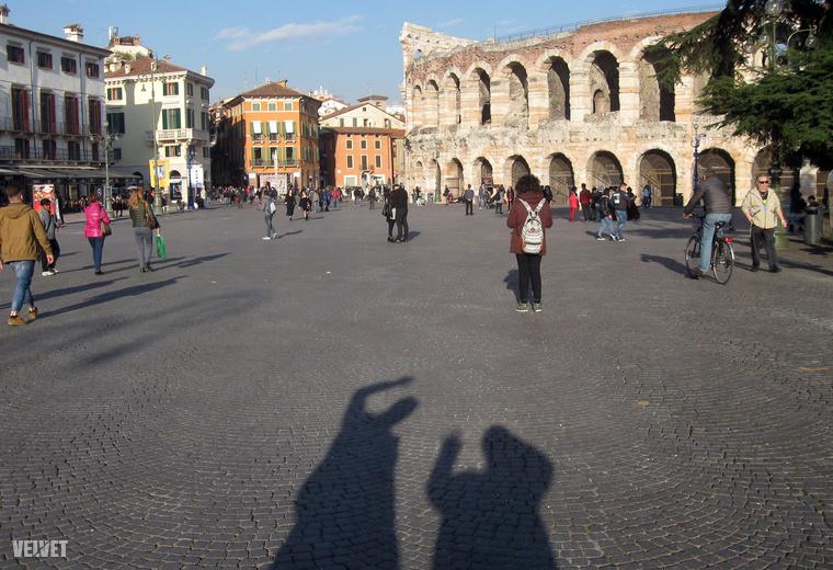 Már nagyon vártuk, hogy eljussunk Veronába!És amikor ott találtuk magunkat a város hatsávos körforgalmában, defektes bal első gumival, azon tűnődtünk, hogy talán mégsem olyan egyszerű vállalkozás.A képen Verona gigantikus főtere az Arénával és velünk.