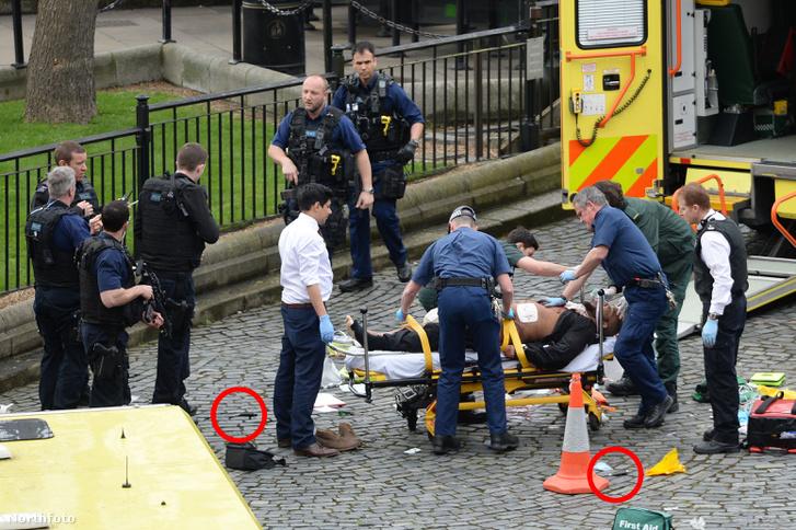 Sebesült férfit, feltehetően a támadót, szállítanak el a helyszínről rendőri biztosítás mellett azon a téren, ahol a merénylő megkéselt egy rendőrt, majd őt is lelőtték. A férfi mellett a földön egy kés is látható.
