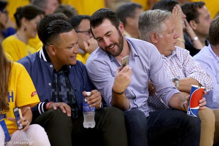 A Detroit Tigers kit játékosa, Miguel Cabrera és Justin Verlander mobiloznak egy NBA-meccs alatt