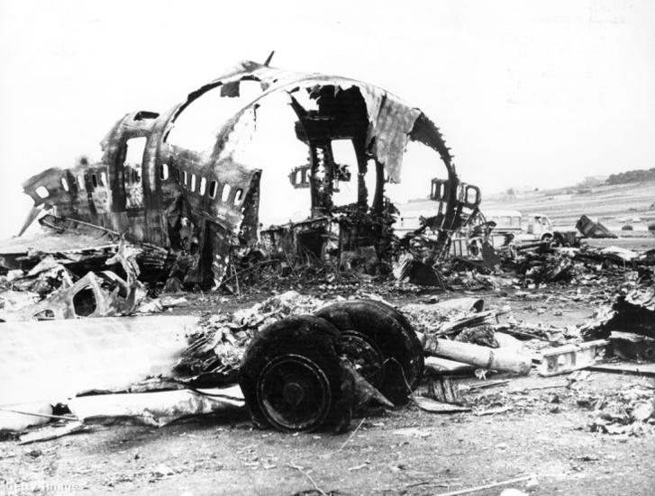 Egy kiégett törzsdarab és egy futómű a reptéri betonon
