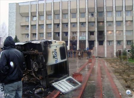Kiégett rendőrségi autó roncsa hever egy kormányhivatal épülete előtt