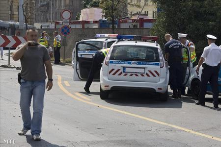 Rendőrök helyszínelnek két rendőrautó mellett (Fotó: Szigetváry Zsolt)