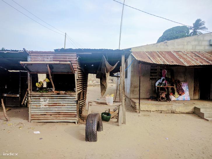 Kisvállalkozók a nyomornegyedben: egy gyümölcsösstand és egy szövőnő a homokkal borított utcán.