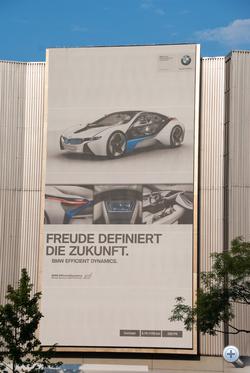 A gyár oldalán tripla méretű óriásplakát hirdeti az örömteli jövőt