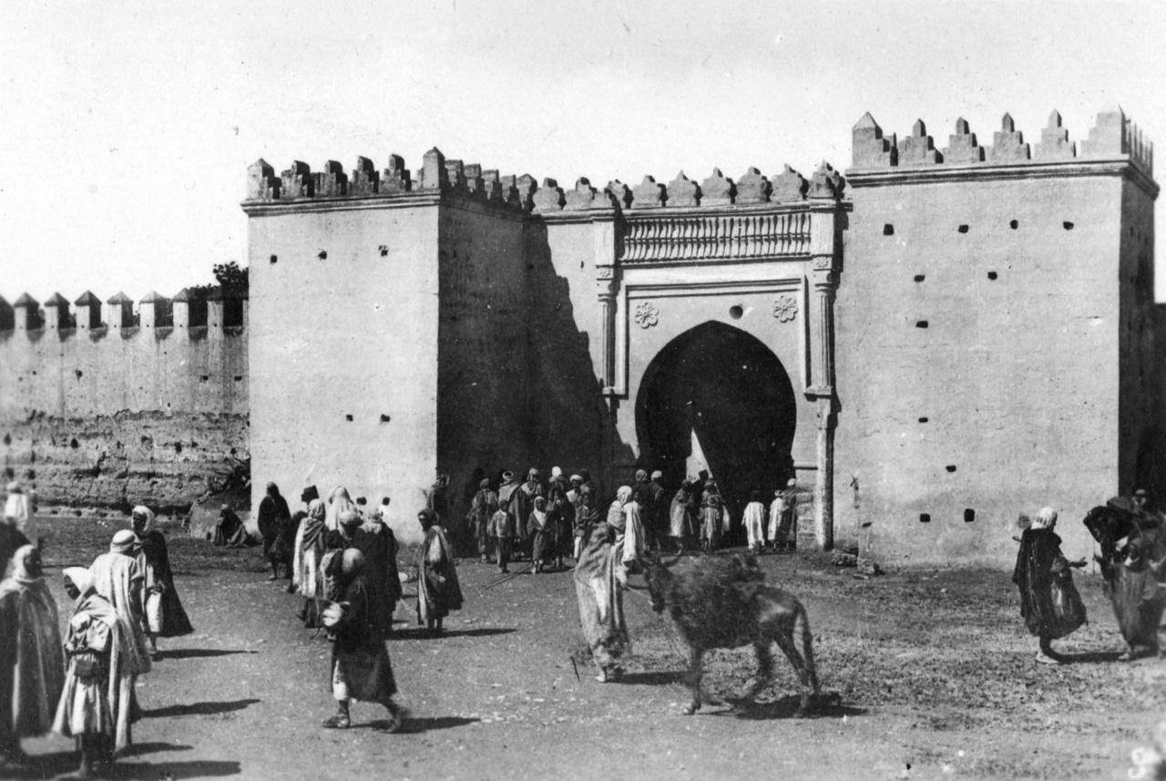 """Marokkó, Oujda városa az algír határ mellett 1935-ben. Életkép berberekkel a medina egyik kapuja előttMarokkó ebben az időben francia protektorátus alatt állt – tudja ezt mindenki akár a történelemkönyvekből, akár a Rejtő-regényekből. Az album rá a tanú, hogy a névtelen fotós személyesen is megnézte magának Marokkót. Egyszer állítólag Rejtő is készült oda. 1931-es, valószínűleg hírverésre használt, zavaros eltűnésekor azt nyilatkozta Az Estnek, hogy Bécsbe indult, """"mert onnan Afrikába akart menni."""" A győri vasútállomás restijében azonban rendőrök igazoltatták, és visszahozták Budapestre. Viszont holokauszt-túlélő apja legendagyártó interjújában azt mondta, hogy Rejtő fogadásból eljutott Algériába – de nem lett légionista, csak dokkmunkás."""
