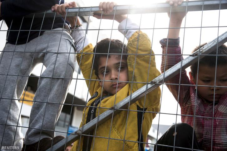 Menekült gyerekek várakoznak egy görög tranzitzóna kerítésénél