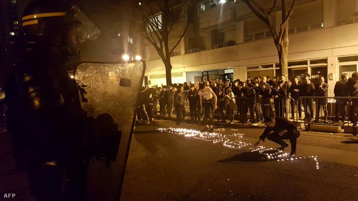 """Az """"erőszak"""" szót rakják ki mécsesekből hétfőn este a rendőri sorfallal szemben Párizs 19. kerületében"""