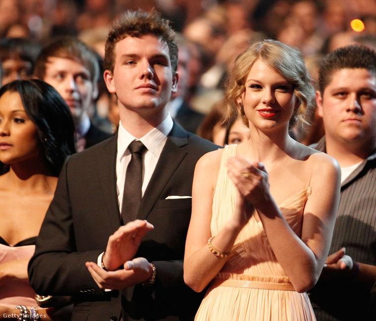 A kép bal oldalán tapsoló Austin Swift ugyanis elindult a sztárrá válás rögös útján: nemrég szerepet kapott a Behálózva című filmben, Pierce Brosnan és Jason Barry oldalán.