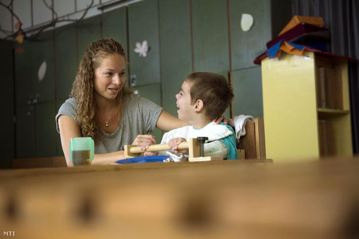 Az önálló étkezést tanulja egy kisgyerek egy konduktor segítségével a Mozgássérültek Pető András Nevelőképző és Nevelőintézetében