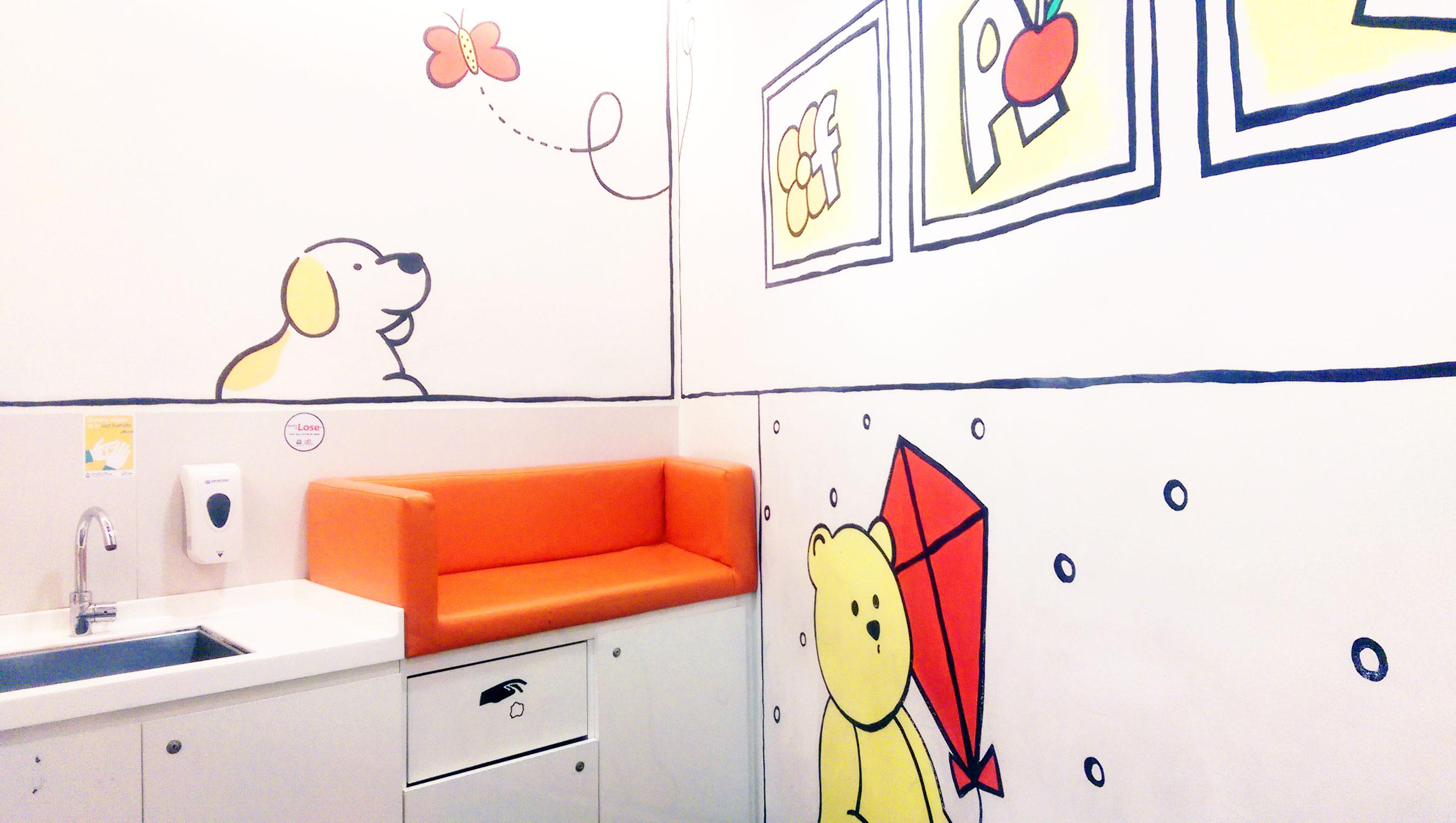 Szingapúr egy másik nagyon barátságos szoptatóhelyisége, mely ugyan letisztult, mégsem kelt túl steril hatást az aranyos rajzok és a narancsszín fel-felbukkanása miatt.