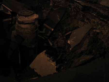 A gödör, közepén a csatornafedélhez vezető betontoronnyal. A beomlás a betongyűrűket is elrepesztette.