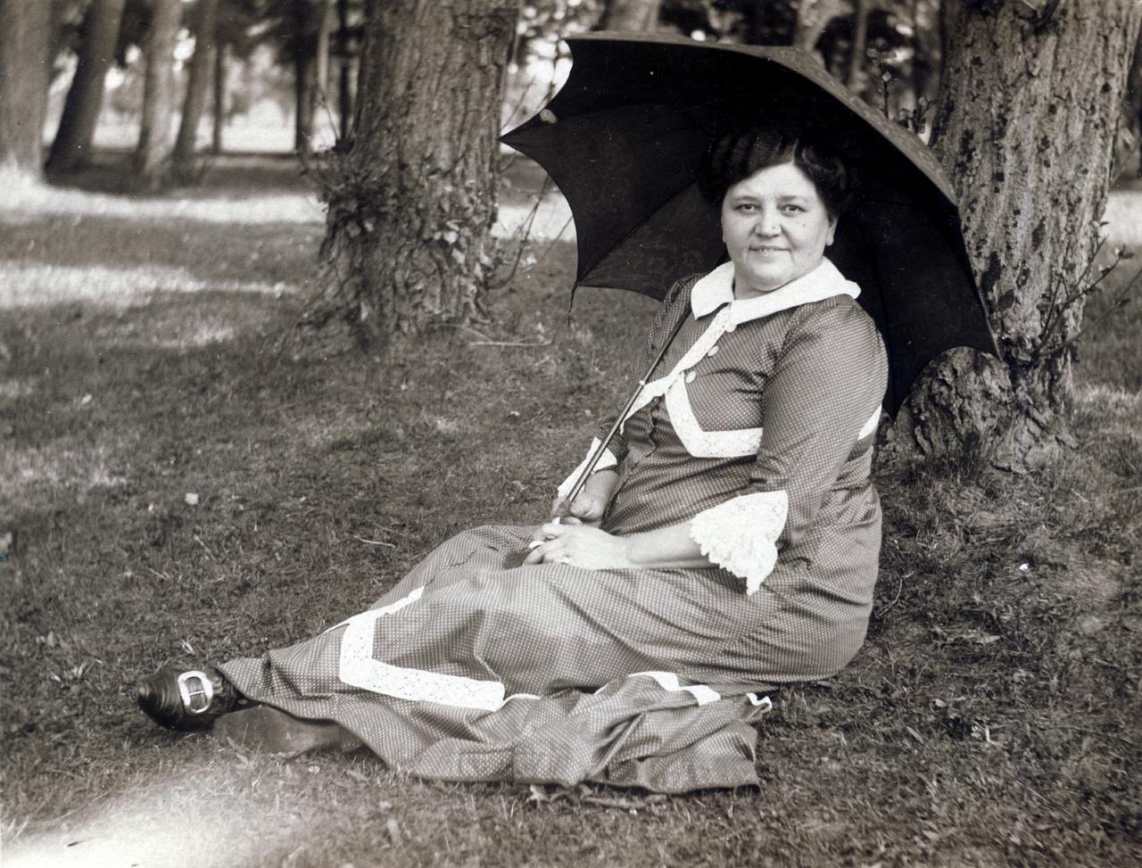 """Erdőssyné újabb napernyője a kollekcióból a Budapesten, 1913-ban feladott levelezőlapon. A csipkebetétekkel bolondított egyszerű szabású ruha láttatni engedi, hogy a József körúti úriasszony falusi tartózkodása alatt mellőzte a fűzőhasználatot. A falusi nyaralás idill és biztonság, szemben például a nagy a nagy fürdőhelyek váratlan veszélyeivel, melyek """"a hozományvadászok, rosszhírű kalandorok, s hírhedt korhelyek találkozó helyei voltak."""""""