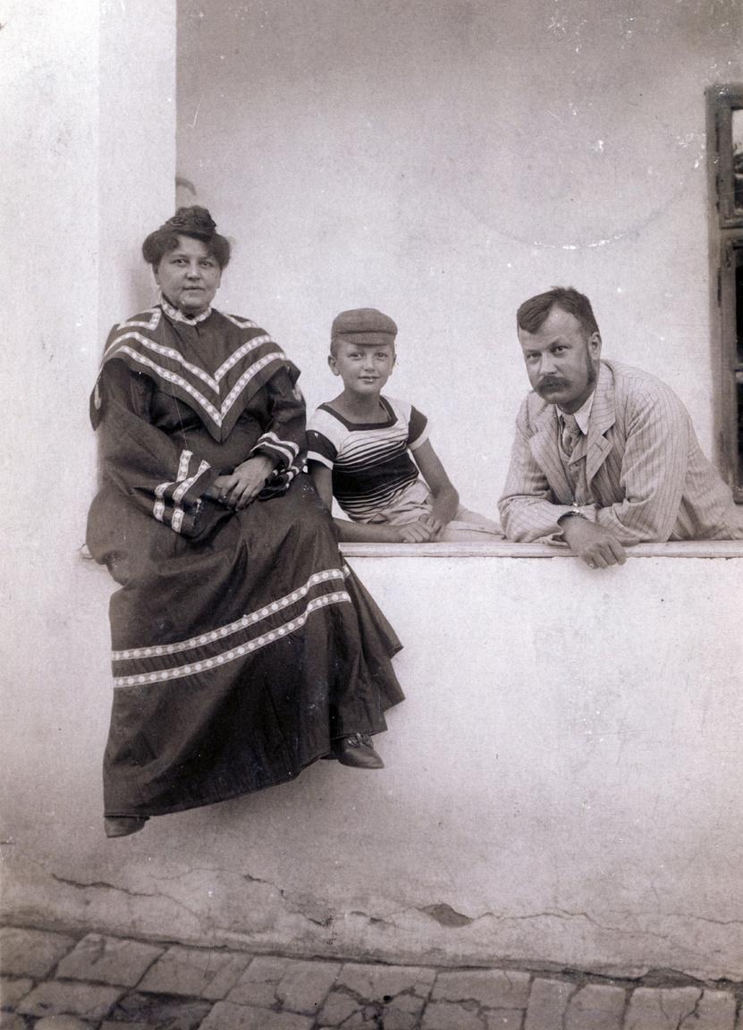 Erdőssyné geometrikus gallérú ruhakölteményben a falusi porta tornácán, férjével és valószínűleg Erdőssy Ida egyik fiával. Saját gyerekük nem született, legalábbis nyomát nem találtuk.