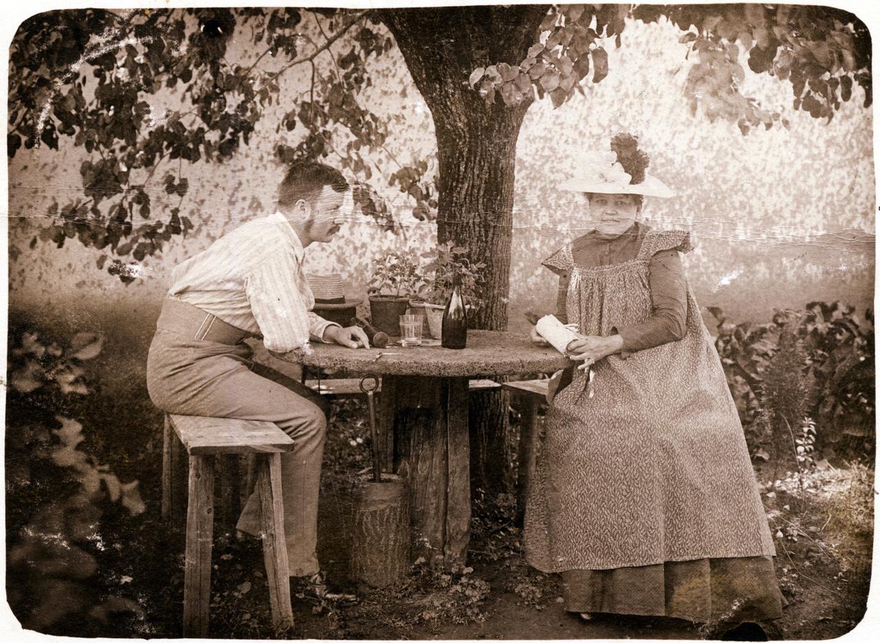 Erdőssy Béla és felesége, az Irmának becézett Mária a szodói (ma Szlovákia) kertben. Vidéki idill, kerti asztal a diófa alatt. A Szodó nevű, a Garamvölgy alsó részén fekvő kisközséget a századforduló környékén alig négyszázan lakták. Vasúttal a zselízi állomásig lehetett jutni, onnan lovaskocsi vitte tovább a pesti nyaralókat. Szodón postahivatal sem volt, Erdőssyék Nagysárón adták fel a levelezőlapokat. Nem derült ki, a nyári hónapokra vajon miért éppen Szodóra menekültek fővárosi lakásukból (József körút 77-79. II. emelet 17). Talán Erdőssy felesége, Irma született a környéken. Mindenesetre a Garam-partra nemcsak fürödni jártak, hanem fontos témája volt Erdőssy munkáinak is.