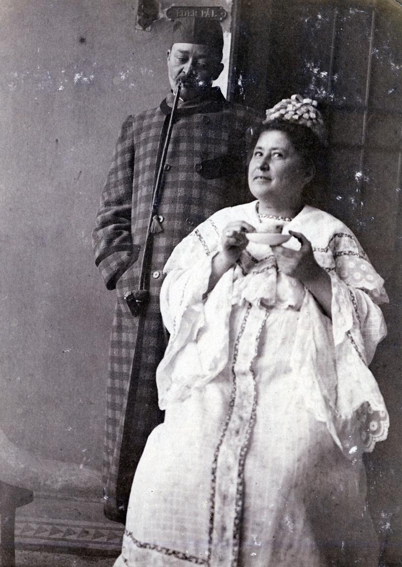 """Sopronyi Éder Pál és felesége, Erdőssy Mariska (a festő testvére) pesti lakásuk előtt. A postai pecsét olvashatatlan, nem segít az évszám és helyszín pontos megfejtésében. A hetven levelezőlapból kibontakozó nyomkövetés szerint 1900 és 1909 között Éderék a belső-ferencvárosi Ferenc tér 9. III. emelet 24.-ben, majd 1909 és 1912 között a Ferenc körút 7. II. udvar I. emeletén és végül az Üllői út 121. III. emelet 19-ben laktak.                         Csibukoló, házikabátos férfi tekint le a rafinált kontytakaróban és decens pongyolában üldögélő feleségére – akárcsak egy népszínmű jelenete a vidéki műkedvelők vagy a ferencvárosi társaskör előadásában. A színpadias beállítás nem véletlen. A családban csak Pádinak becézett Éder Pál levéltári segédként kezdte, végül az 1920-as években a IX. kerületi előljáróság segédhivatalának főigazgatójaként nyugdíjazták. Mindeközben verseket, elbeszéléseket írt a Bolond Istók, a Pikáns Lapok, az Üstökös című lapokba, és több darabját játszotta a Népszínház.                         Meg kell említenünk Erdőssy Mariska súlyos, illem elleni vétségét, melyet ráadásul nyílt levelezőlapon követett el: """"Művelt, finom nő"""" még ebédhez sem ült le pongyolában, nemhogy egy csésze teával a kezében a gangon."""