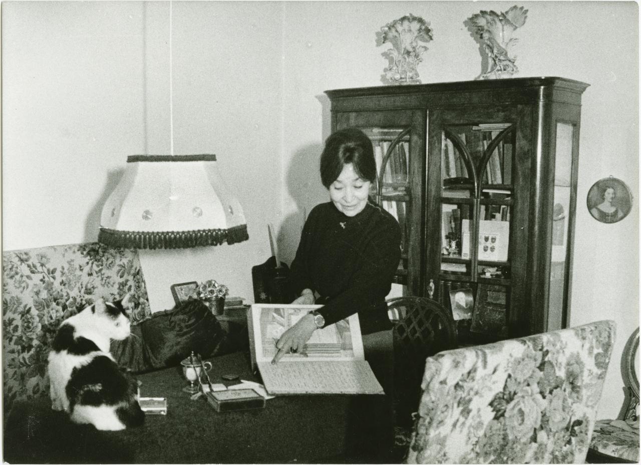 """A fotó valószínűleg 1980-ban készült a Júlia utcában. Szabó Magda Földes Annának, a Nők                         Lapja újságírójának mutatja régi biblia-gyűjteményének legkedvesebb darabját, melyet a                         Régimódi történet bemutatójára kapott Illés Endrétől. A falon családi portrék, a szekrényekben                         könyvek és családi porcelánok, mind-mind régtől fogva az írónő kísérői és történetek hordozói: """"A                         tárgyak: a memóriám. Emlékeztetnek, figyelmeztetnek, mi minden történt egykoron. Sírnak és                         nevetnek, az egész lakásom reagál arra, ami bennem itt és a falakon kívül történik."""" A macskák                         és más állatfajták is egész életében társai voltak, többször felbukkantak műveiben. Például Ifi                         istennő, a tarka bundás macska, aki együtt menekült 1944 nyarán a Szabó családdal                         Debrecenből egy bihari szőlőhegyre, az 1947-ben megírt tízénekes elbeszélő költemény, a Szüret                         egyik szereplője lett."""