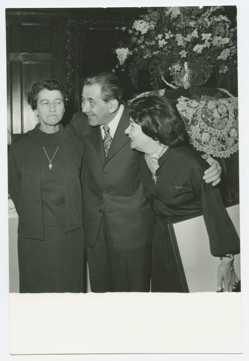 """Galgóczi Erzsébet engesztelhetetlen, Aczél György és az írónő már tud nevetni. A fotó                         valószínűleg 1978-ban készült, amikor Galgóczi és Szabó Kossuth-díjat kapott. Az 1956 után átírt                         kultúrpolitika befogadta és magasra emelte Szabó Magdát. Aczél próbálta jóvátenni, amit 1949-                         ben Révai egyetlen telefonnal tönkretett: """"A kiadók, amelyekről azt hittem, elfelejtették, hogy volt                         valaha egy, az én leánynevemet viselő költő, mind megkerestek, anyagot kértek – a kör, amelyet                         1949-ben egy adminisztratív intézkedés kettémetszett, összeforrt megint. 1958-ban megjelent a                         Freskó, a rákövetkező évben megkaptam rá a József Attila-díjat. Aczél György, mikor kezembe                         adta a dobozt, a dekrétet, azt mondta: 'Ez most az a díj. A Baumgarten. Nevessen már!'                         Nevettem, de aztán elfordultam tőle, és elsírtam magam. [...] Most újra itt futhatunk a manézsban,                         Szobotka is, én is, hány kört szaladjunk még, hogy soha többé ne kételkedjenek abban, hogy ide                         tartozunk? És mit bírnak még az izmaink? Az a díj ez, persze hogy az a díj. Csak közben elmúlt                         az ifjúság."""""""