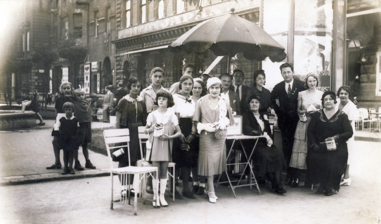 Elegáns társaság gyűjt adományt a rokkantak részére a Liszt Ferenc téren. A napernyő alatt, jobb oldalon fátylas kalapban Goldenberg Lili, Kati mamája. A háttérben terézvárosi utcagyerekek és a Japán kávéház (ma Írók Boltja) székei.