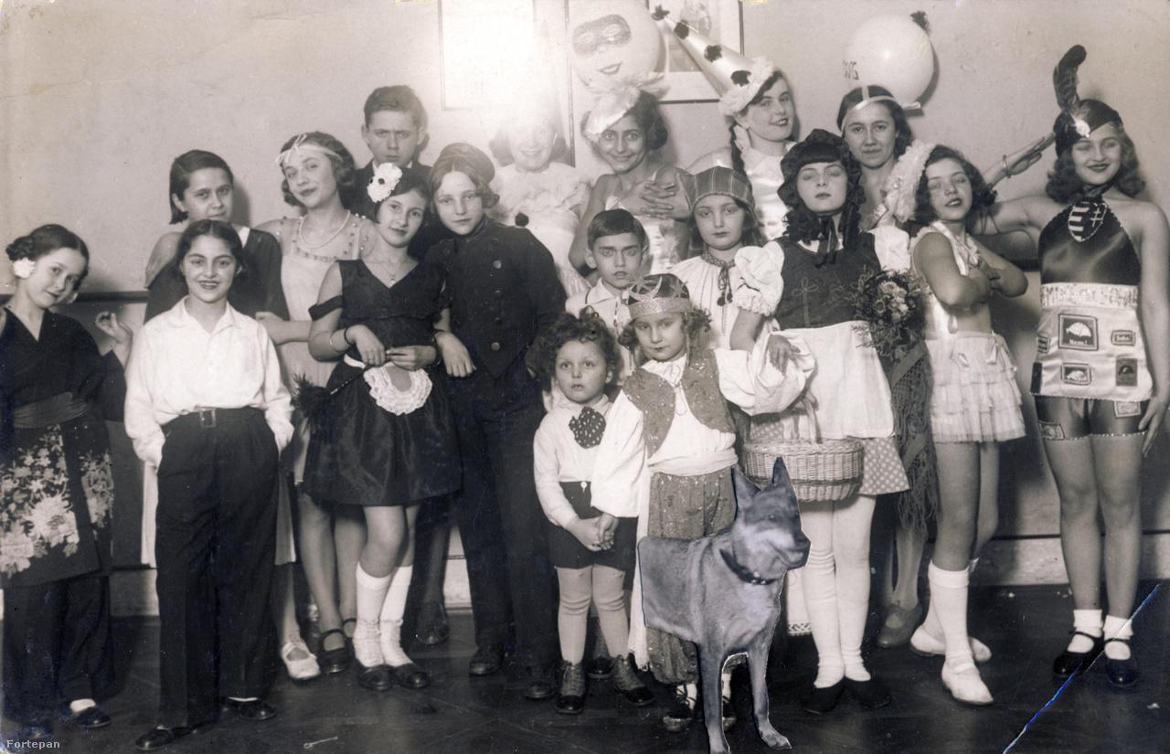"""Az Est-lapok 1934-es gyermekfarsangján. A farkaskutya később csatlakozott a csoportképhez                         A Vígszínházban megrendezett mulatságon volt álarcos felvonulás, jazz és operett, szerpentincsata, bábszínház. A legérdekesebb azonban az élő mesekönyv és gyerektörténelem volt, melyekhez hetekkel előbb újsághirdetésben keresték a szereplőket.  """"Piroska és a farkas szerepére Ráth Katót és gyönyörű farkaskutyáját tartottuk a legalkalmasabbnak"""" – írja a fotó alatti újságkivágás. Igazi kortörténeti jelkép a kép jobb szélén álló darutollas kislány 'Nem, nem, soha!'  és Nagy-Magyarország díszítésű selyemruhában."""