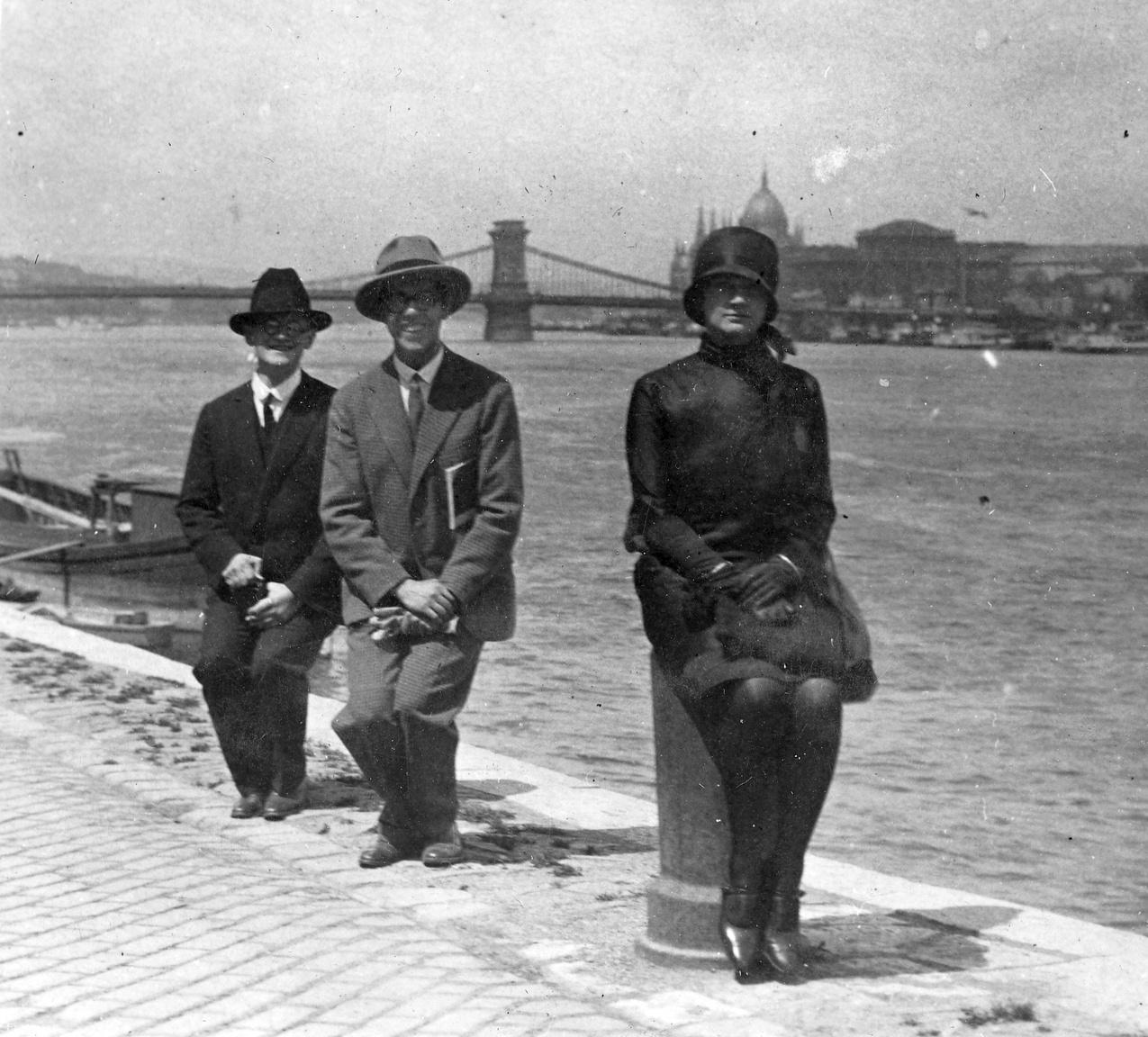 A budai alsó rakpart, háttérben a Lánchíddal, 1928                         A két szemüveges úr fütyül a sötét ruhába öltözött hölgy komolyságára, akit nem vesz le a lábáról holmi képeslapra kívánkozó Budapest-panoráma. A vízen most kis faladikok, de a rakpartnak ezen szakaszán gyakran angol, francia, olasz naszádok is vesztegeltek – ilyenkor az árboc és ágyú közt kifeszített kötélen olasz gatyákat és ingeket lengetett a szél.