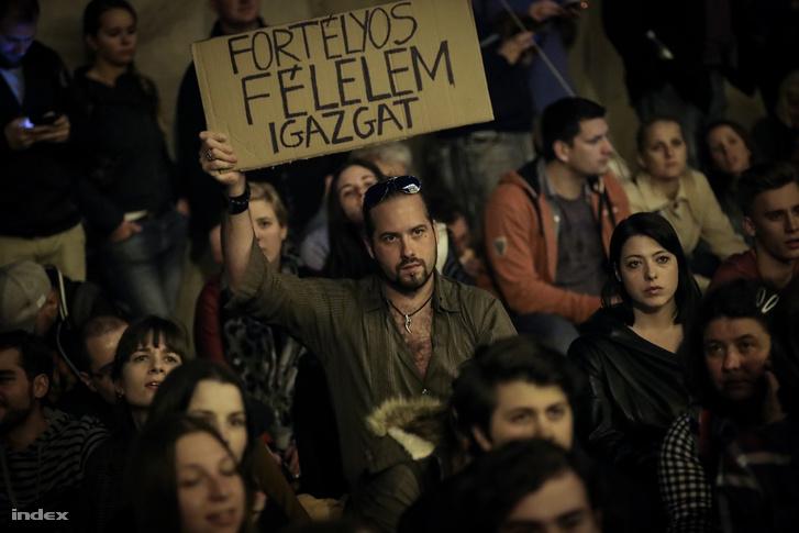 Táblát tart a kezében egy férfi a CEU-ért szervezett demonstráción, a Parlament előtt.