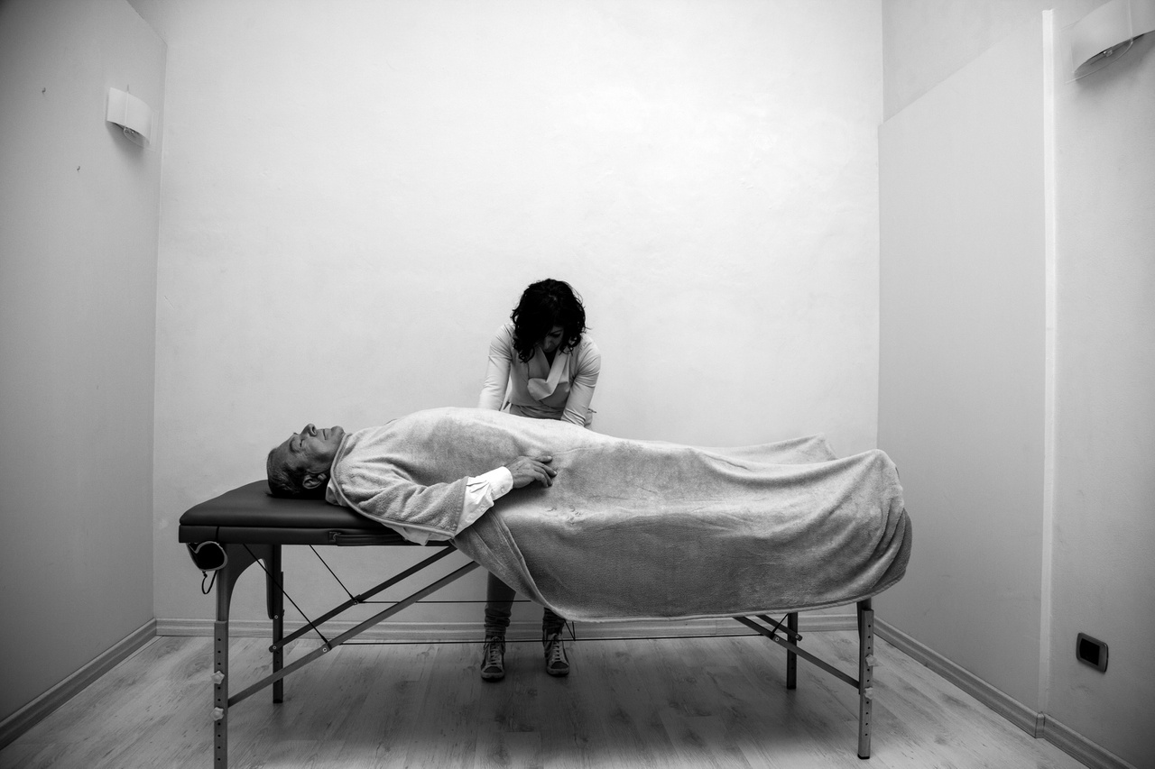 Giuseppe Manfredi (született 1949-ben) és lánya Daniela Manfredi (született 1975-ben), Casale Monferrato, Alessandria, Lombardia. Giuseppe lánya segítségével reikizik. A mellhártyarákban szenvedő férfi négy hónappal a kép készítése után meghalt. Az azbesztózis következtében kialakult betegséget rendkívül nehéz legyőzni, egyelőre kísérleti gyógymódok léteznek a kezelésére. Giuseppe Manfredi nem vehetett részt ilyen kezelésben.