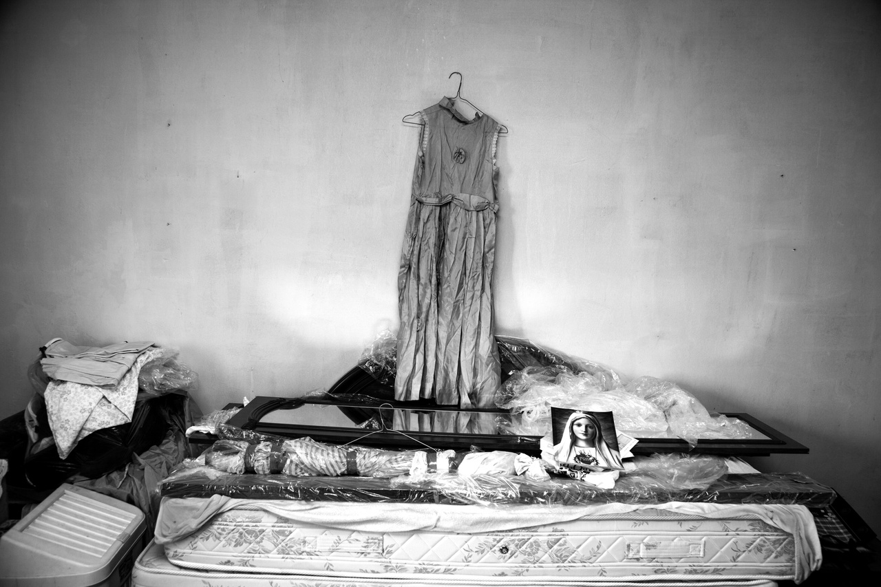 """Pietro Condello bélrákban elhunyt feleségének ruhája a házaspár elhagyott házában. A mellhártya-meszesedéssel küzdő férfi felesége halála után elköltözött Casale Monferratóból. """"A halállal élsz együtt ebben a városban"""" – mondta a férfi, aki biztos benne, hgy felesége halálát a belélegzett azbeszt okozta. Egyes tanulmányok szerint lehet összefüggés az azbesztózis és a bélrák bizonyos fajtái között."""