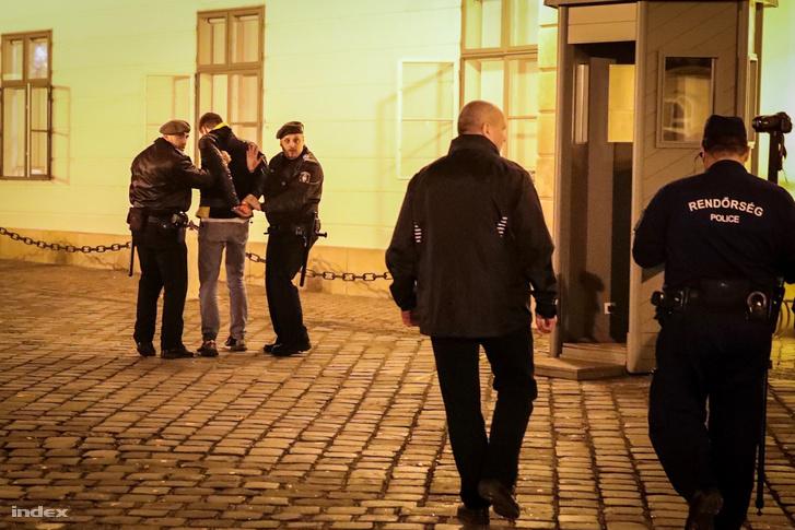Gulyás Mártont vezetik el a rendőrök a Sándor Palotta előtt, hétfőn este