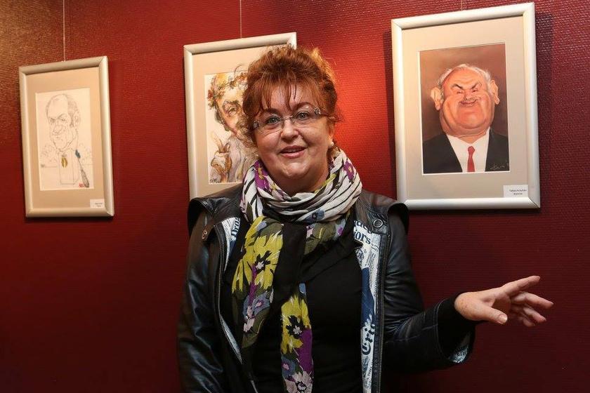 Kövér Ildikó mutatja a Hofi Gézáról készült karikatúrákat a kiállítás megnyitóján.