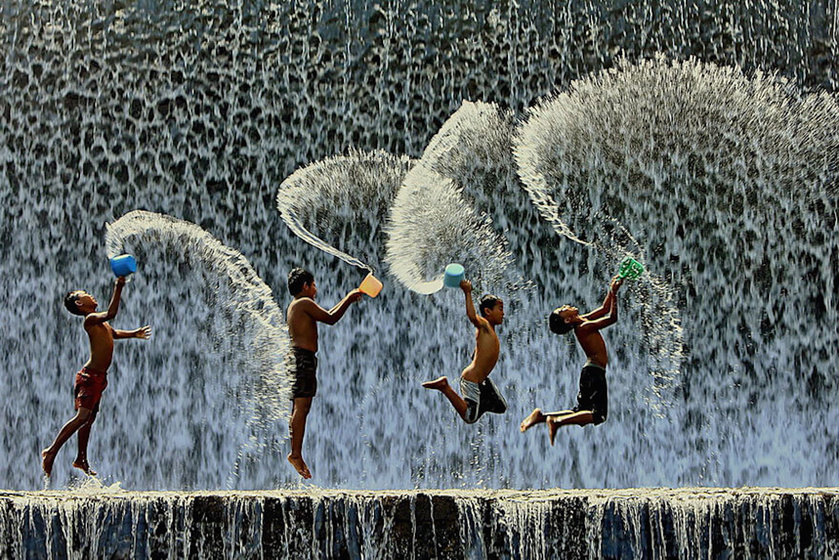 Zubogó víz, egy pár műanyag vödör és túláradó életöröm. Indonéziában így szórakoznak a gyerekek monszun idején. Fotó: Agoes Antara