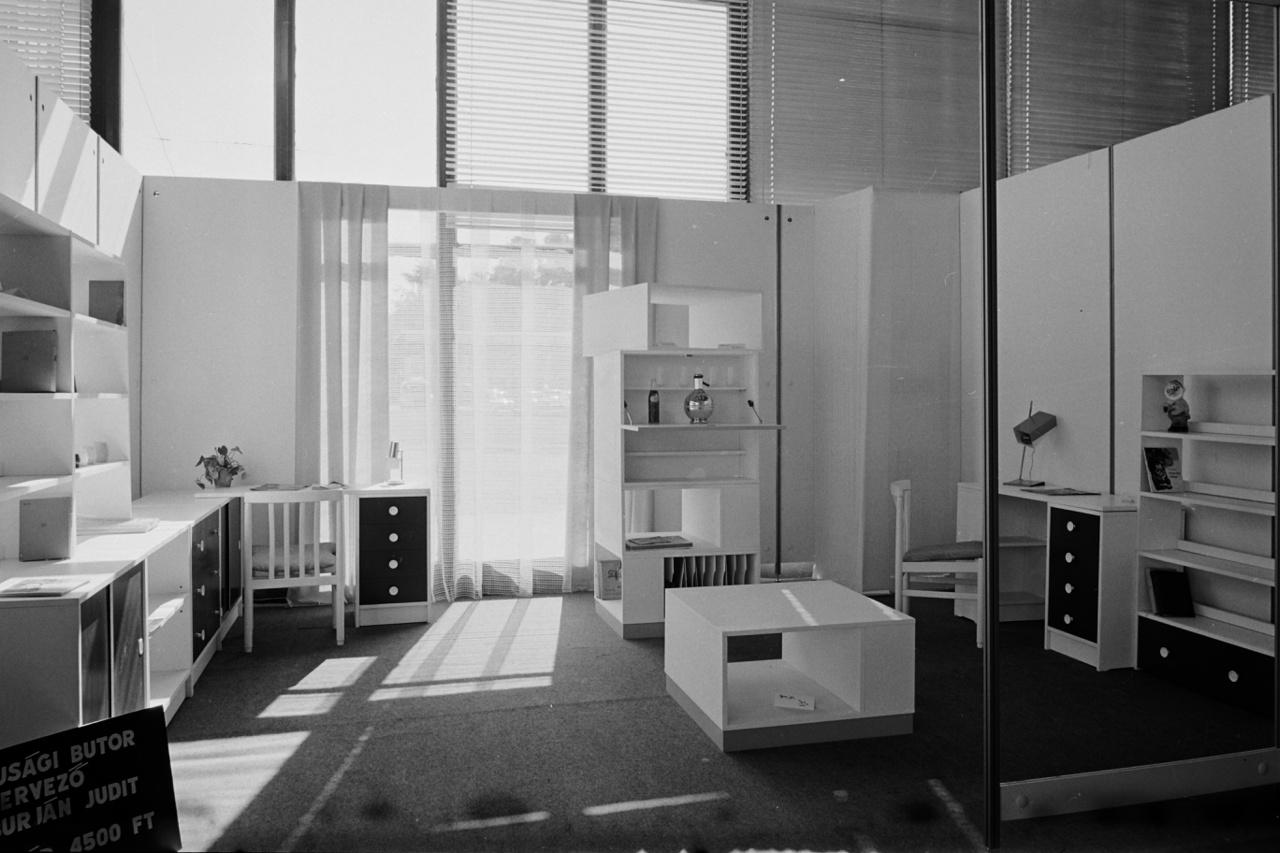 ÖT (kép: 44)                         A központosított rendszer egyszerűsítette ugyan az alapanyagok beszerzését, a gyártást, és az értékesítést is, ám színtelenné tett a kínálatot, nagyjából mindenki ugyanazt gyártotta. Ezért teljesen átszervezték a bútoripart.                         Nyolc üzemet ipari övezetbe költöztettek, és gyárrá alakítottak, felszerelve őket a legmenőbb olasz és eneszkás gépsorokkal. A cél az volt, hogy a teljes hazai keresletet kielégítsék, és a bútorok olyan minőségben készüljenek, hogy azokat nyugaton is el tudják adni, kemény líráért, márkáért, frankért.