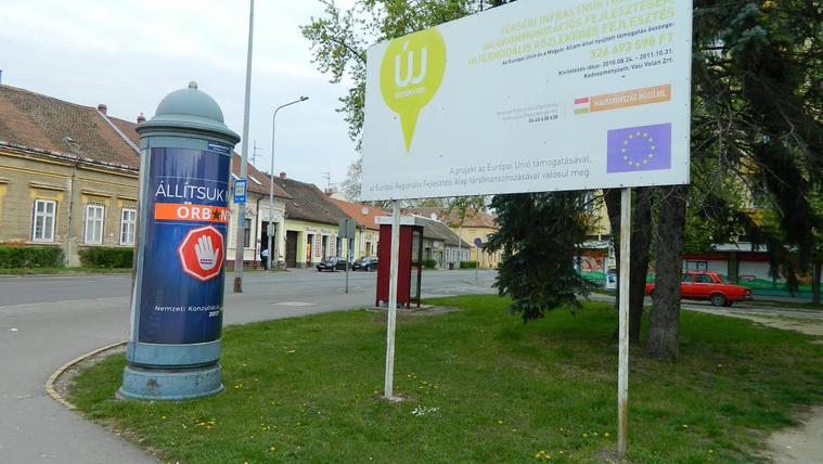 Átragasztott Brüsszel-ellenes kormányzati plakát az uniós támogatás információ táblája mellett Szombathelyen