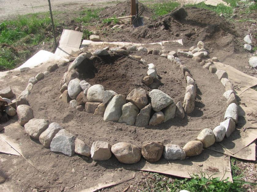 Az alsó réteg lényege a vízelvezetés és a védelem, erre kavics vagy sóder is használható. Ezután kezdheted el a spirál külső építését: alulra a legnagyobb kövek kerüljenek, majd fokozatosan haladj a kisebbek felé! Nézd meg, hogyan alakítsd ki ezt a kis csodát a kertedben!