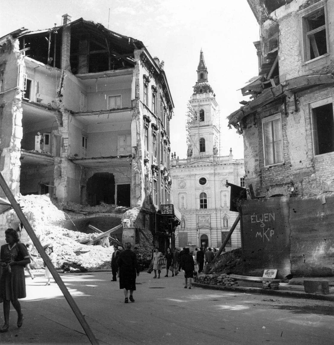 """Az éljen a Magyar Kommunista Párt feliratának erős kontrasztot ad a háttérben lévő szervita templom. Mindez a belvárosban, 1945-ben. Kissé furcsa, hogy az üzenetet propagáló forma csupa nagybetűvel írta az éljent, kissé megzavarodott az """"a"""" betűnél, aztán az MKP-nál a """"k"""" óriási lett végül. Vallásosabb lelkületűek beleláthatnak egy eléggé elszúrt krisztogramot is ebbe, ami nagyjából egy X ( a görög khi) és egy P (ró) egyben. Vagy valami máriás jelmondat rövidítését. Mindenesetre az épülő templom mellett ez a nehezen összehozott felirat mondjuk egy külföldinek sokkal inkább tűnhet valami jámbor egyházi üzenetnek, mint a gyilkos diktatúra hírnökének."""
