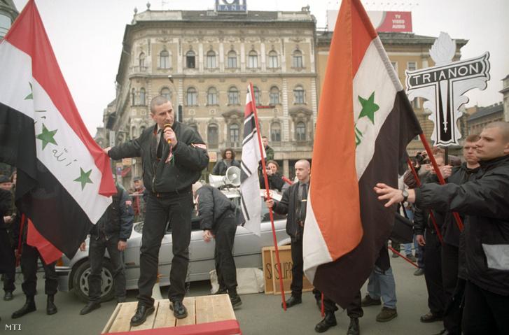 Szabó Albert az MNSZ elnöke a rendezvény szónoka iraki zászlók között beszél a Magyar Népjóléti Szövetség (MNSZ) Blaha Lujza téren tartott megemlékezésén 1999-ben.