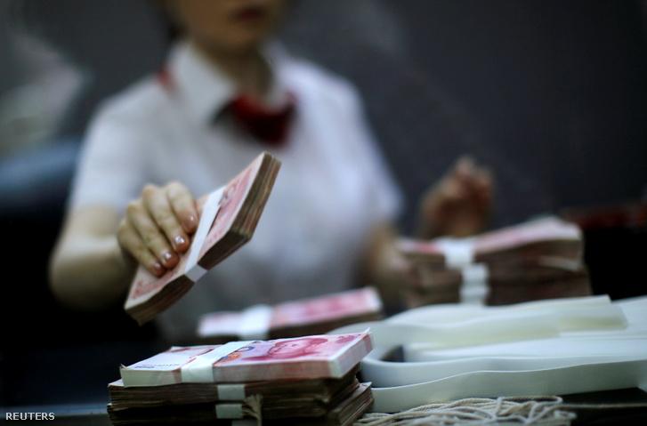 A Kínai Ipari és Kereskedelmi Bank alkalmazottja pénzt számol egy sanghaji bankfiókban